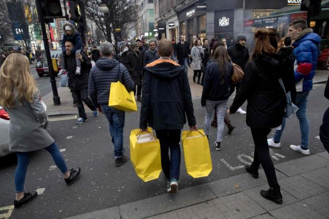 A woman carries shopping bags full of items down Oxford Street today